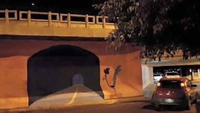 street artist painted a road runner tunnel on a wall  someone tried to drive through it