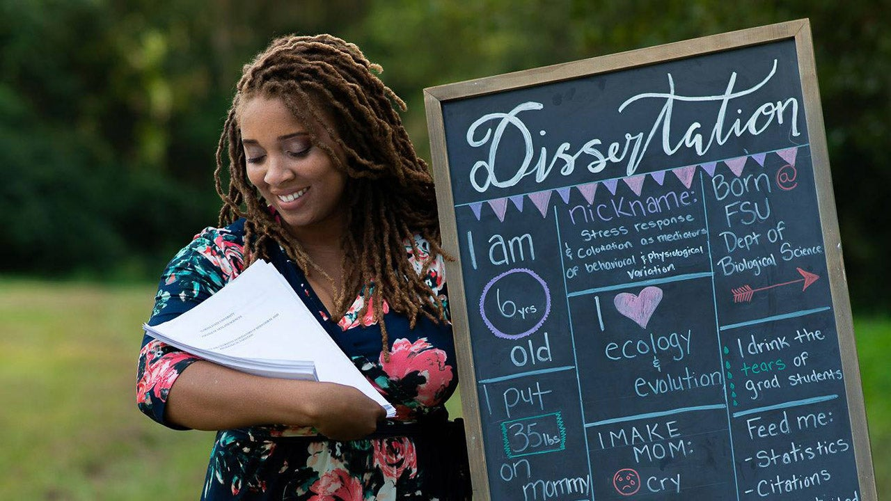 Woman Poses With Dissertation in Maternity Photo Shoot Celebrating Doctorate