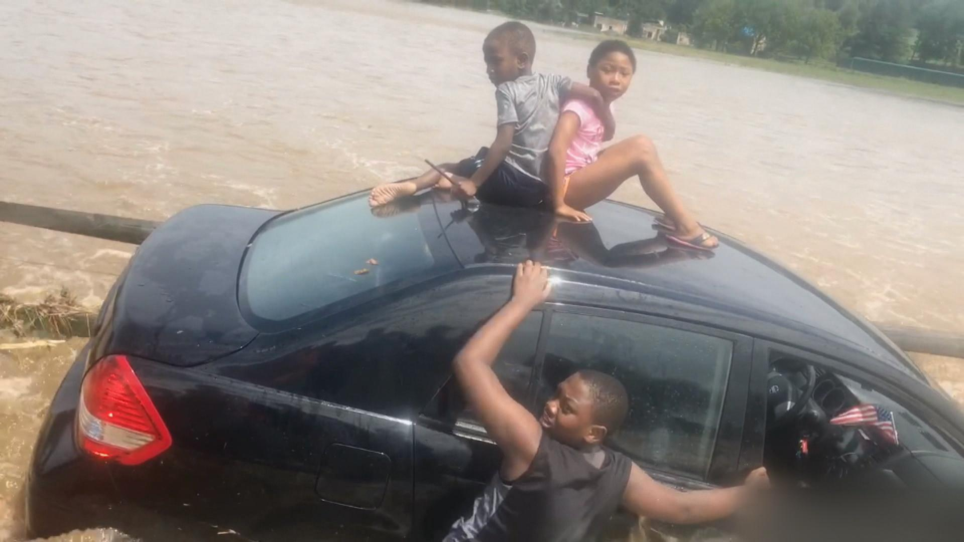 Family Trapped in Car by Raging Flood Waters Rescued by Backhoe Driver