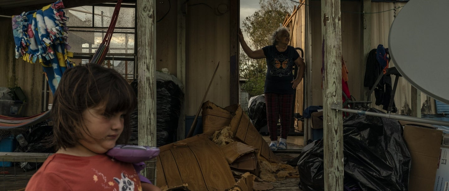 A child stands on the sidelines as her family surveys the damage to their home.