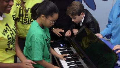Students test their hands at one of the brand new pianos gifted by 'A Bronx Tale.'