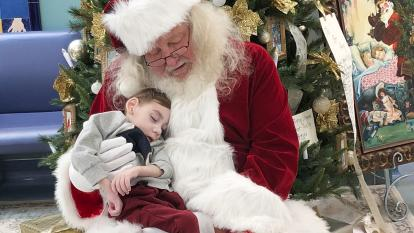 Santa poses with Miles Agnew, 2, as he sleeps on his lap.