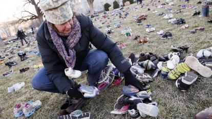 A volunteer places shoes in the emotive display, meant to be a call to Congress to take action on gun reform