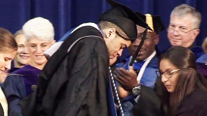Ty Williams makes his way across the commencement stage after being paralyzed during a game his sophomore year.