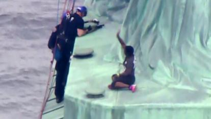 Therese Patricia Okoumou waves authorities away as they try to rescue her.