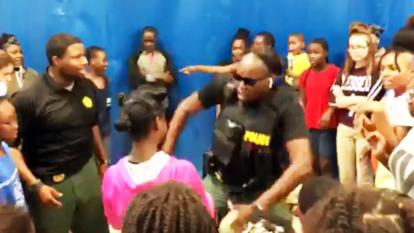 Officer Belita Salters challenges a young girl to a dance-off.