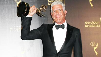 Anthony Bourdain holds up a trophy he won at the 2016 Creative Arts Emmy Awards.