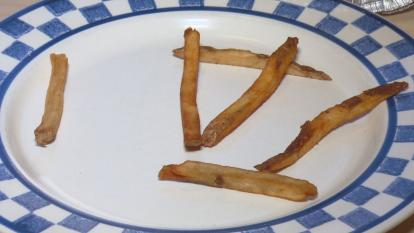 Six french fries on a plate