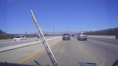 A ladder slammed into a woman's windshield as she was driving.