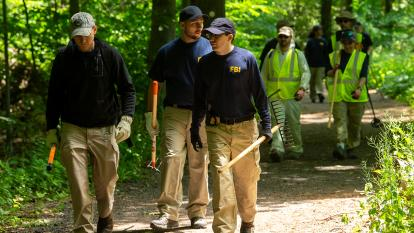 An FBI team searches the woods in New Canaan, Connecticut.