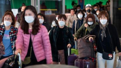 people wearing masks arrive at Los Angeles Airport