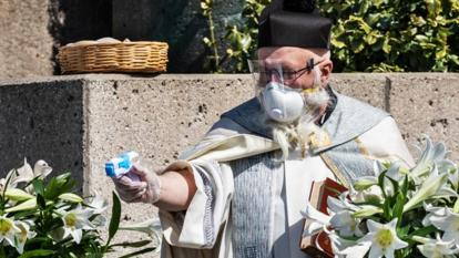 Father Tim Pelc of the St. Ambrose Parish sprayed holy water at cars passing by with a squirt gun.