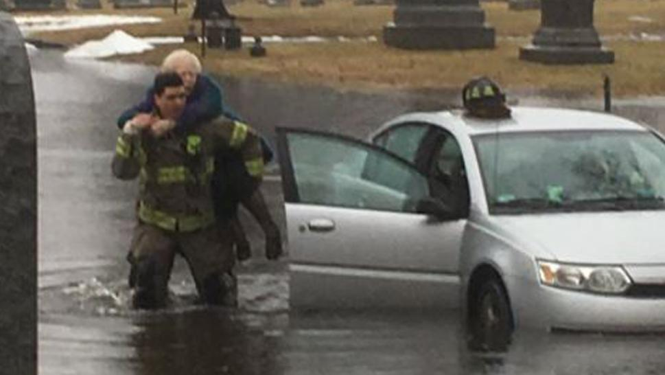 One firefighter left his helmet on the hood of the car as he carried one of the women on his back while he waded through the icy water.