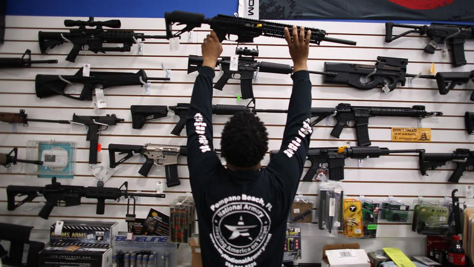 Mike Acevedo puts a weapon on display at the National Armory gun store on April 11, 2013 in Pompano Beach, Florida.