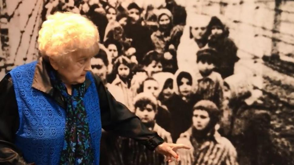 Eva Mozes Kor points to a photo of herself as a child being liberated from Auschwitz.