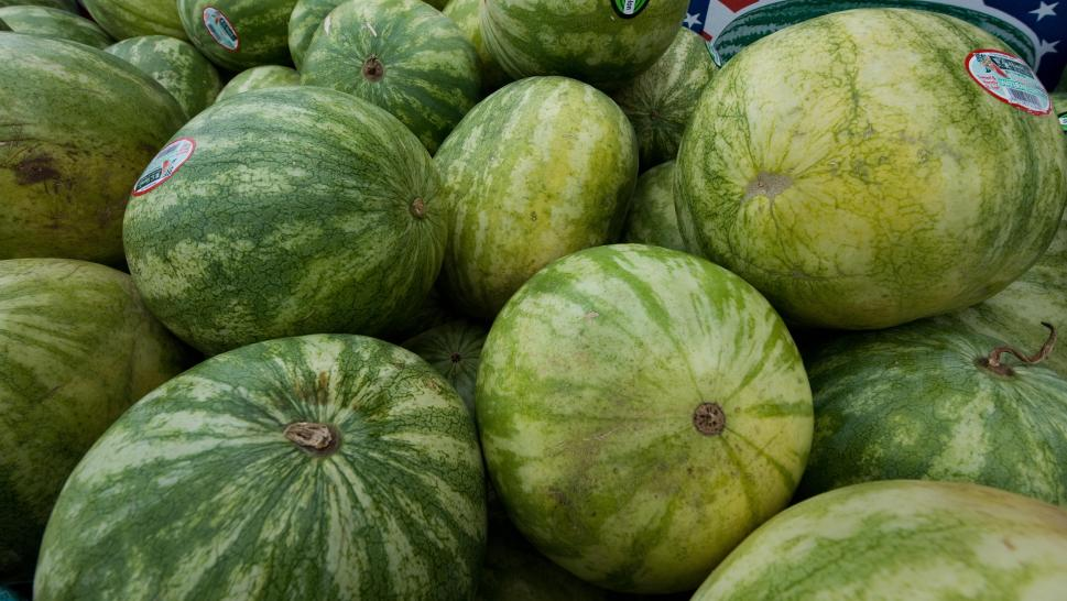 A boy underestimates the weight of watermelons at a grocery store.