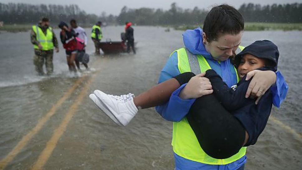 North Carolina volunteer carries Keiyana Cromartie after the child's family was rescued from their home.