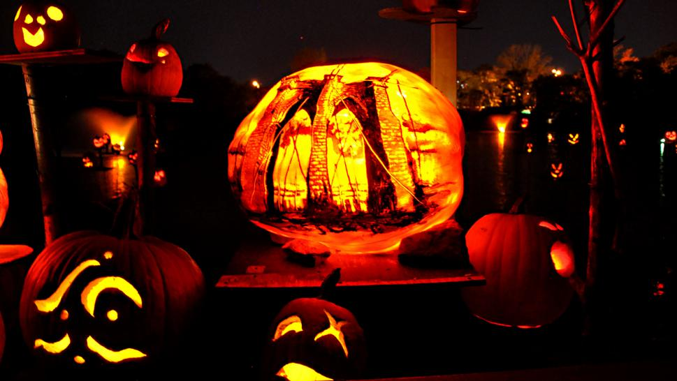 A ghastly cityscape glows on the surface of this pumpkin.