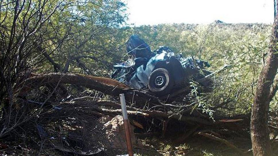The car crashed through a right-of-way fence and plummeted 50 feet before landing in a mesquite tree.