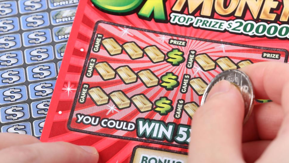 A person scratches off a lottery ticket.