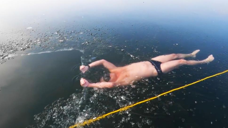 Man swimming under ice