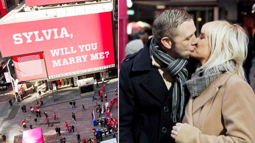 Bernard Barrett and Sylvia Condon share a sweet kiss under their billboard.