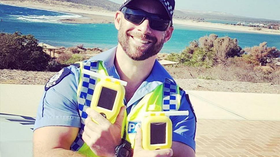 Kalbarri Senior Constable Paul Ellison is photographed with two breathalyzers.