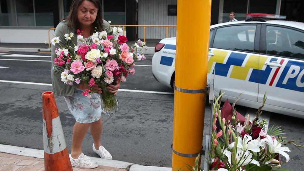 A mourner lays flowers in tribute to the victims of New Zealand's mass shooting.
