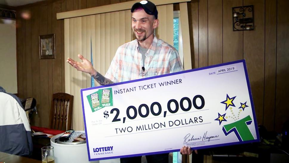 Timothy Seratt holds up his lottery winnings.