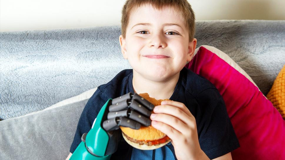 Freddie Cook, 8, has a bite of a burger he holds using both hands.
