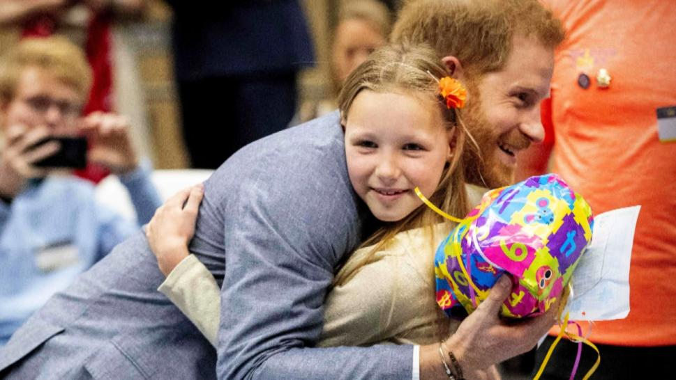 Girl giving a gift to Prince Harry