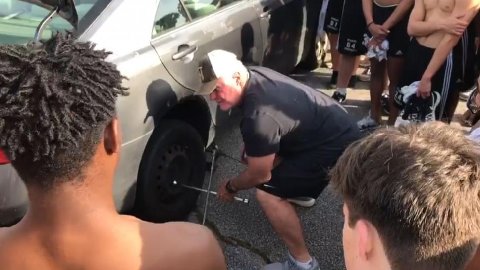 Defensive line coach Steve Carter teaches his team to change a tire.