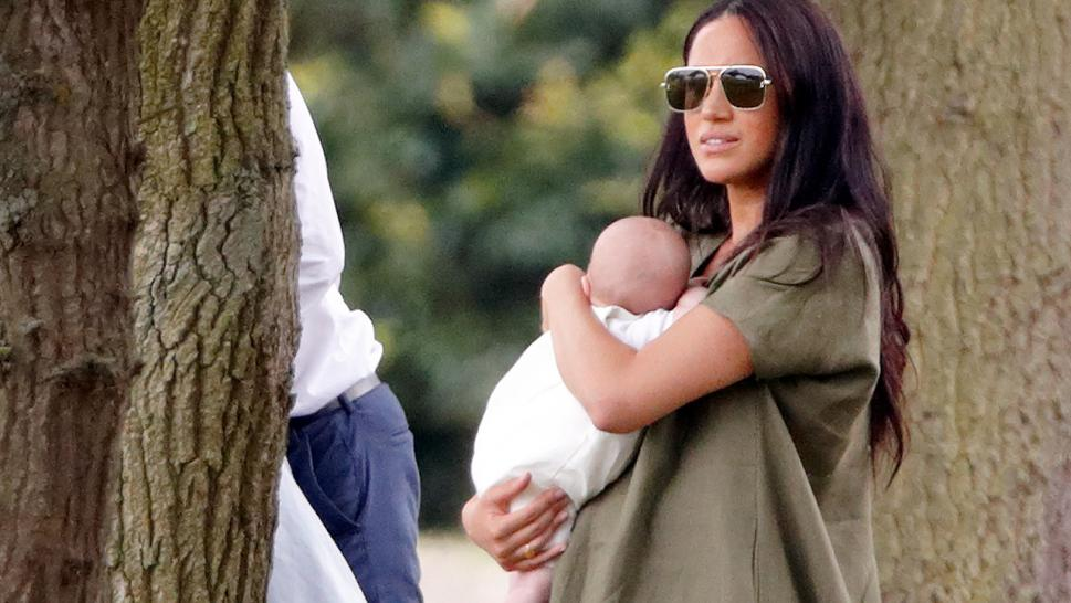 Meghan Markle was photographed affectionately cradling her 9-week old son while watching a polo match with other members of the royal family on Wednesday.