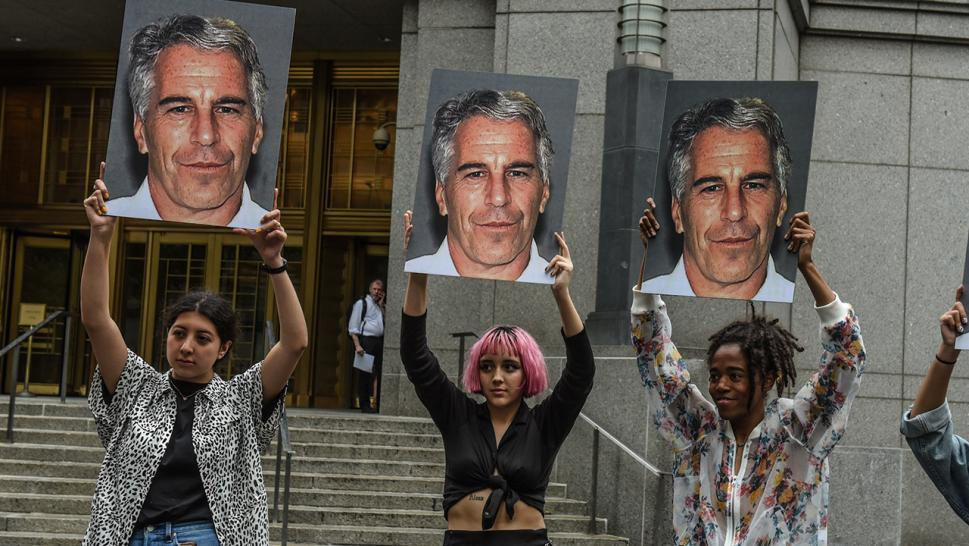 Protesters hold up signs with Jeffrey Epstein's face on them.