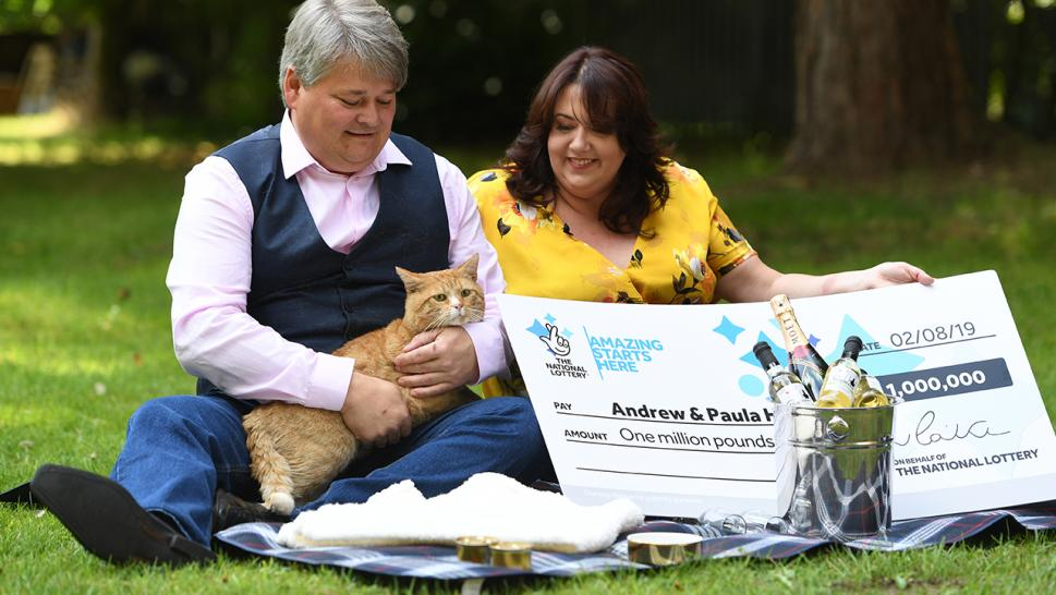 Andrew and Paula Hancock pose with their cat, Shortcake, after winning the lottery.