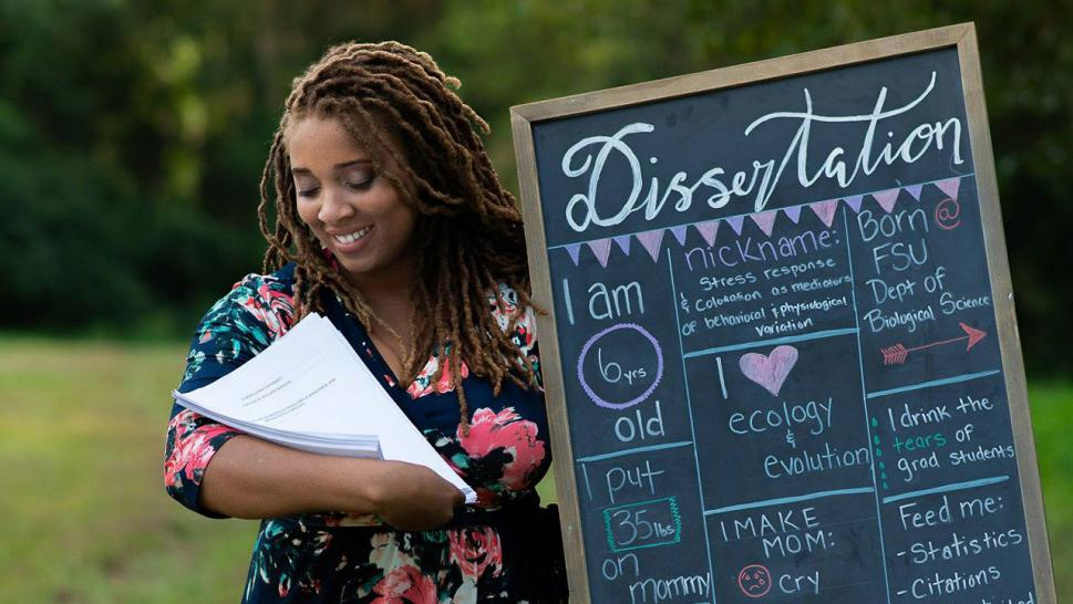 Woman poses with dissertation for maternity shoot