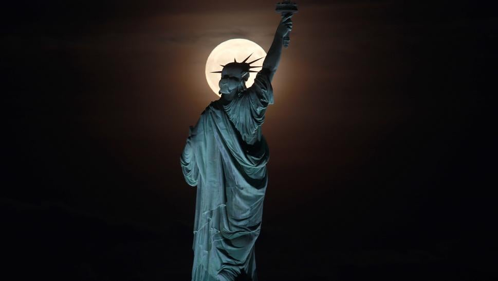 The Statue of Liberty is seen at night.