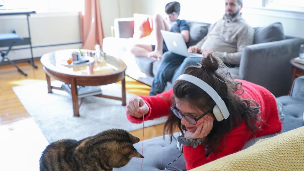 Cecilia Conway plays with the family cat, Darla, while her brother James sits on the couch and her and step-father John Taraborelli works from home in Cranston, RI on March 16, 2020.