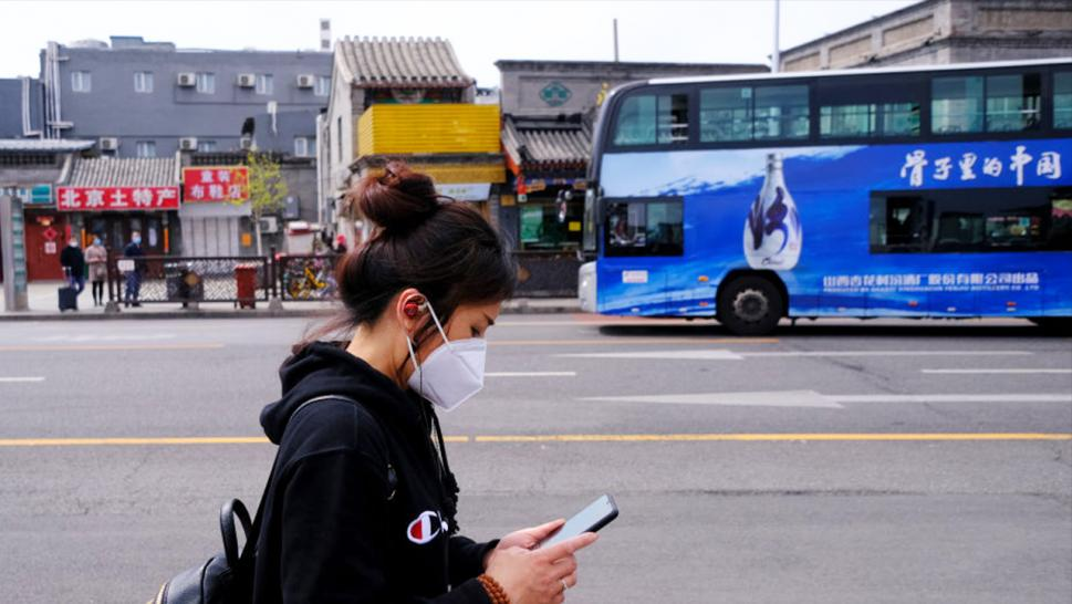 A woman uses her cell phone while wearing a mask as part of precautionary measures against the spread of the COVID-19 on commercial street on April 01, 2020 in Beijing, China.
