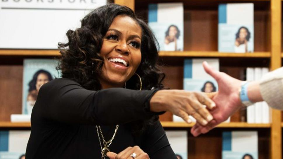 "Michelle Obama meets a fan during her book tour for ""Becoming."""