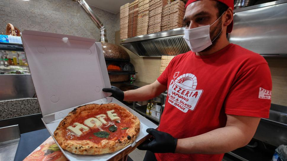A pizza maker in Naples, Italy shows off a pie with a special message.