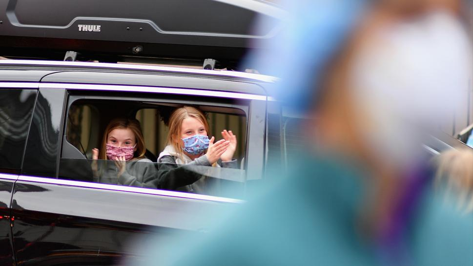 Two kids cheer on New York City hospital workers from a car.