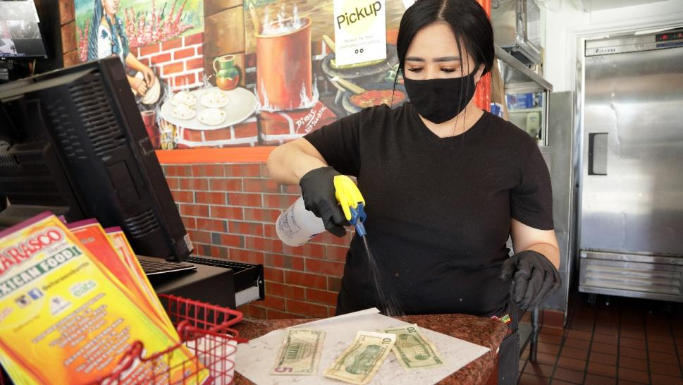 aricela Moreno, manager at El Tarasco in Marina del Rey, disinfects cash at the restaurant.