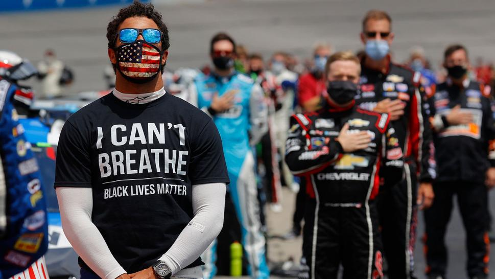 "Bubba Wallace, driver of the #43 McDonald's Chevrolet, wears a ""I Can't Breath - Black Lives Matter"" T-shirt under his fire suit in solidarity with protesters around the world taking to the streets after the death of George Floyd on May 25 while in the custody of Minneapolis, Minnesota police, stands during the national anthem prior to the NASCAR Cup Series Folds of Honor QuikTrip 500 at Atlanta Motor Speedway on June 7, 2020 in Hampton, Georgia."