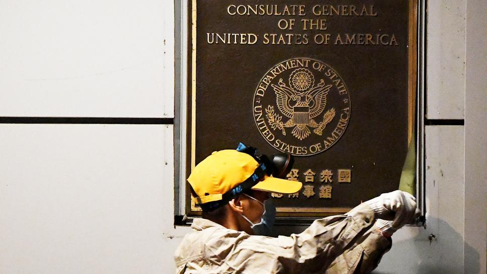 A Chinese worker removes a plaque as officials prepared to close the U.S. consulate in Chengdu, China, Monday morning.