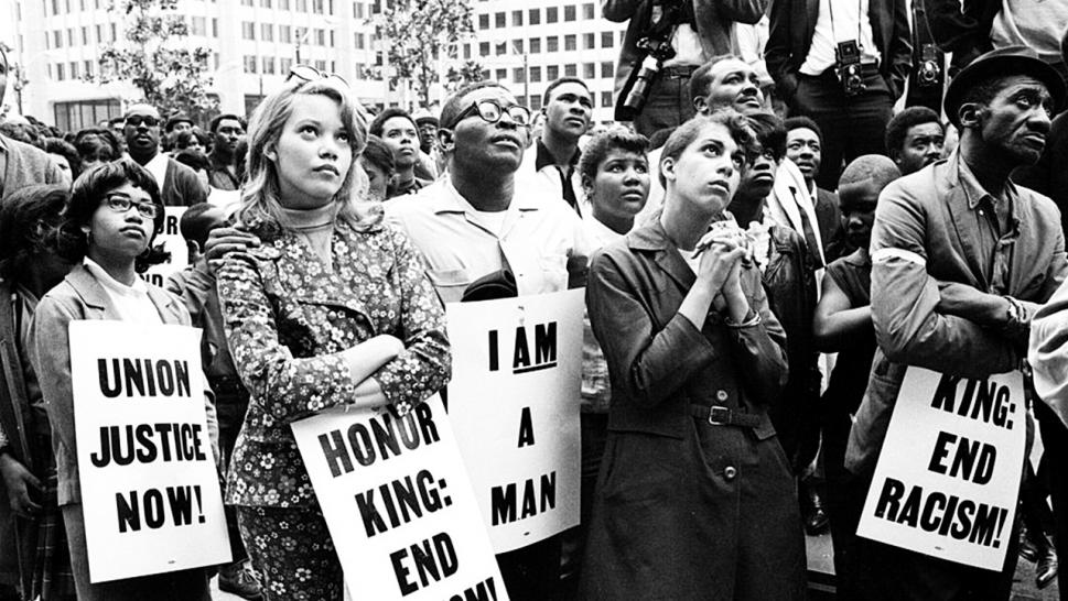 A group of demonstrators holding signs reading 'Union Justice Now', 'Honor King: End Racism!' and 'I Am A Man' march in protest soon after the assassination of Dr. Martin Luther King, Jr., Memphis, TN, April 1968.