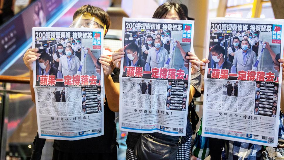 Hong Kong residents hold up Apple Daily's Tuesday newspaper in protest.