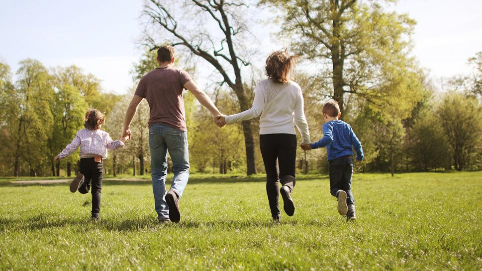 A family running together in a park.