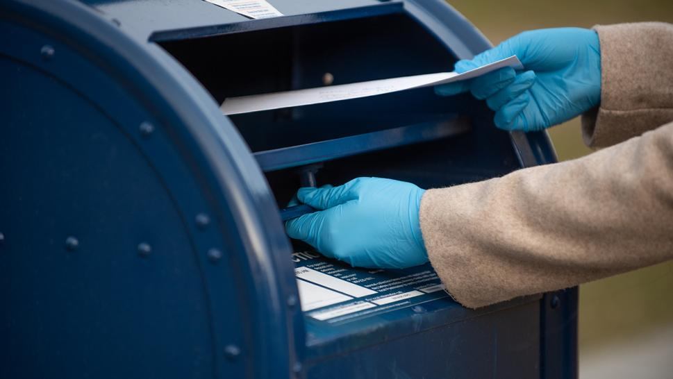 Person mailing letter in USPS mailbox.