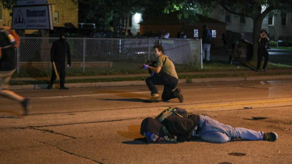 A man on the ground was shot in the chest as clashes between protesters and armed civilians who protect the streets of Kenosha